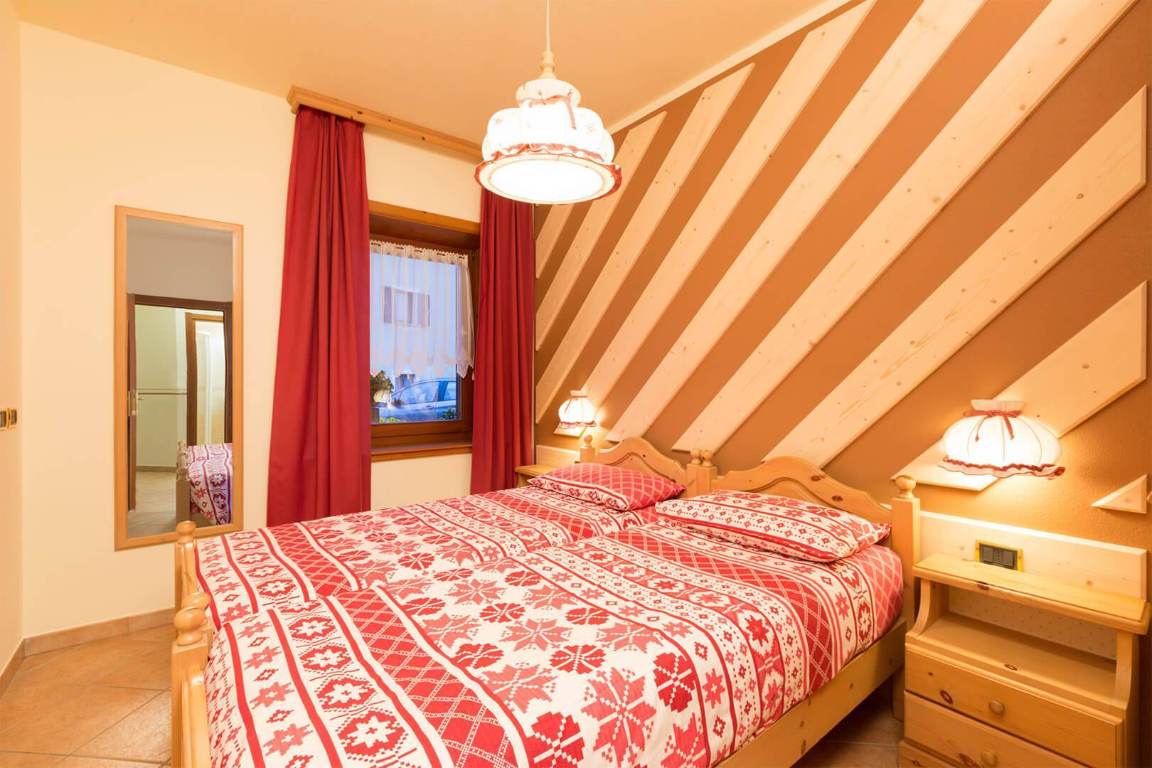 Wooden wall and double bed in Livigno